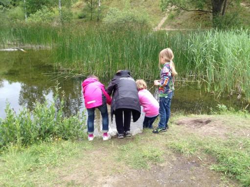 Pedagog och barn släpper tillbaka djur i vattenbryn.