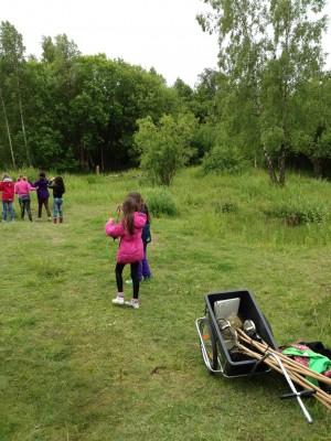 Barn går iväg i skogen med håvar i en vagn.