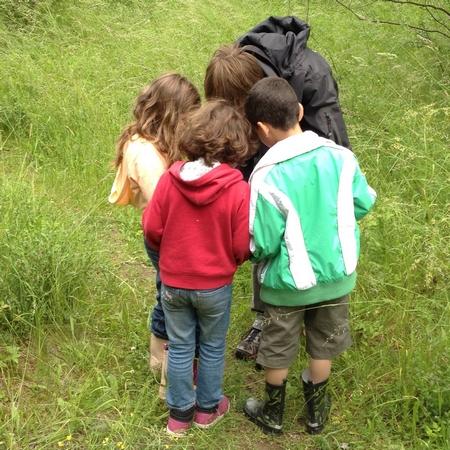 Kvinna visar tre elever något i naturen.