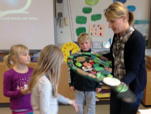 Pedagog lyfter upp konstverk så att barnen kan se.