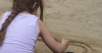 Flicka ritar hjärta i sanden.