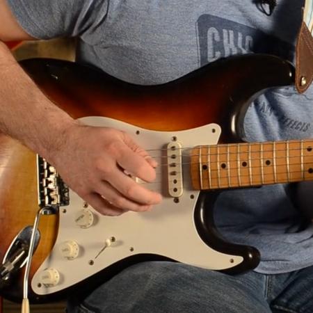 Hand spelar på elgitarr.