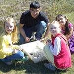 Pedagog visar tre elever saker samlade i vit plastbalja.