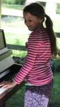 Flicka spelar på piano.
