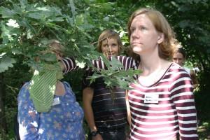 Kvinna har handen i en påse samtidigt som två kollegor står vid sidan om.