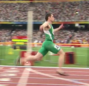Man i grön löpardräkt springer över mållinje.