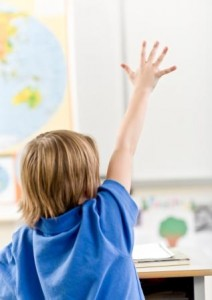 Elev räcker upp handen i klassrum.