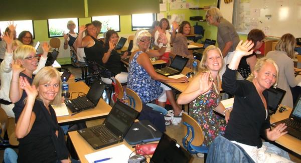 Pedagoger sitter i skolbänkar med datorer framför sig.