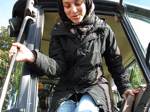 Flicka hoppar ut ur traktors förarhytt.