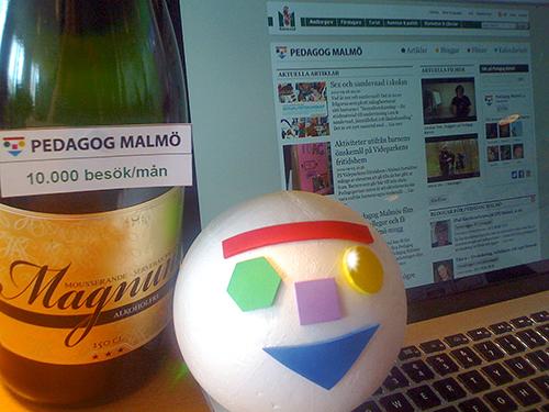 Champange och en uppslagen dator med Pedagog Malmö på skärmen.