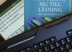 Tangentbord ligger över läsplatta och boken Att skriva sig till läsning.