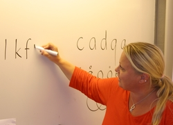 Kvinna skriver bokstäver på whiteboard.
