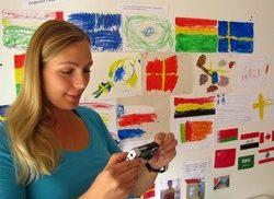Kvinna står framför vägg med flaggor och filmar med digitalkamera.