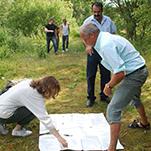 Pedagoger lägger ut stort papper på marken i skogen.