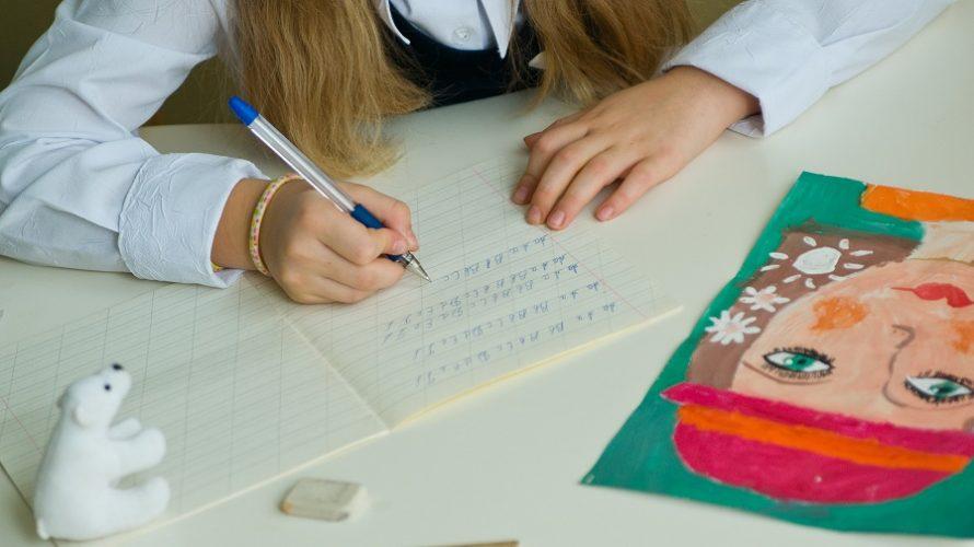 Flicka skriver i texthäfte.