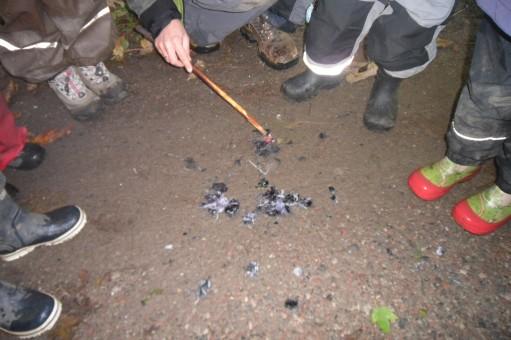 Barn med gummistövlar tittar på slajm på marken.
