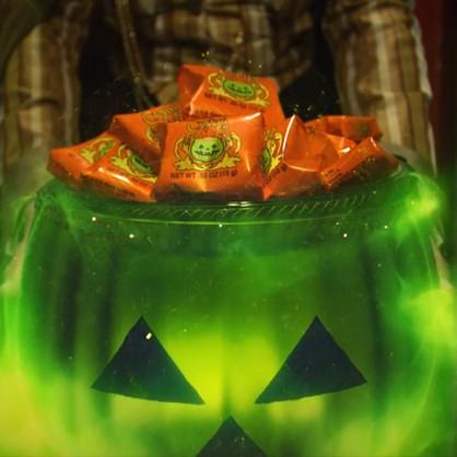 Grön halloweenpumpa med godis i.