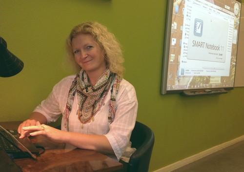 Kvinna sitter framför en interaktiv skrivtavla.