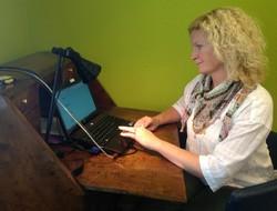 Kvinna sitter vid dator.