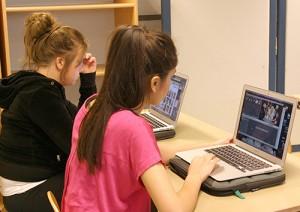 Två elever jobbar på datorer.
