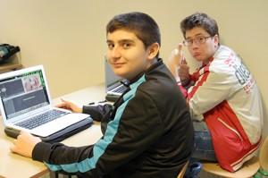 Två elever med varsin uppfälld dator.