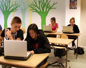 Elever sitter i skolbänkar med datorer uppfällda.
