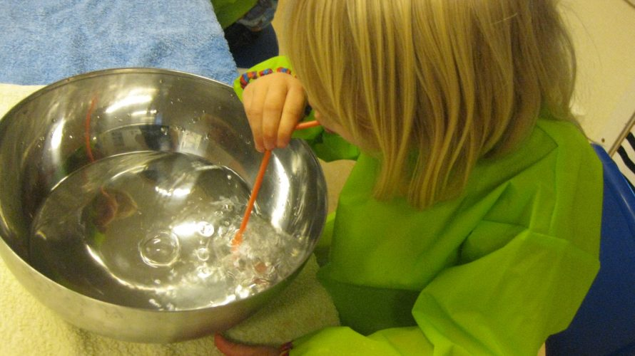 Barn bubblar med hjälp av sugrör i en stor skål med vatten.