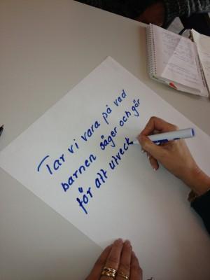 Hand skriver ner tankar om barns vilja på papper.