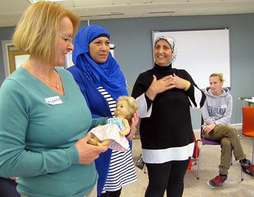 Tre kvinnor håller i en docka.