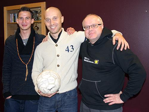 Tre personer står och pratar och håller i en boll.