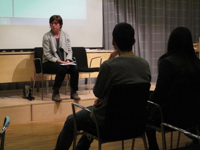 Kvinna sitter på stol framför publik.