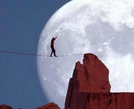 Man balanserar på lina framför måne.