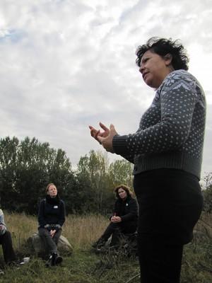 Elizabeth Florez föreläser för pedagoger som sitter på stenar på äng.