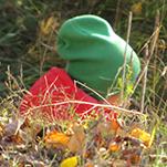 Person med grön mössa sitter nedanför backe.