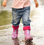 Barn går med gummistövlar i vattenpöl.