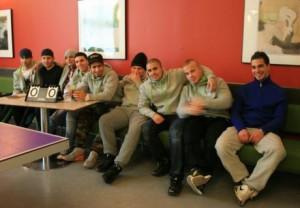 Nio elever sitter i soffa vid pingsbord.