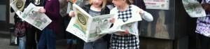Barn står med uppslagna tidningar.