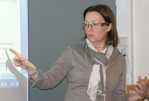Carola Rehn-Lindberg pekar på en projicerad presentation.