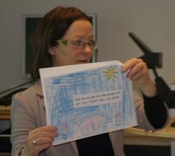 Carola Rehn-Lindberg håller upp en teckning med text på.