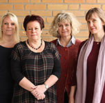 Fyra kvinnor står framför gul tegelvägg.