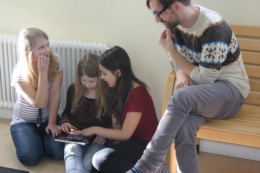 Pedagog hjälper tre flickor som spelar på ipad.