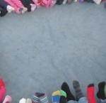 Ring bildad av barns fötter som sträcks in i mitten.