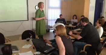 Helena föreläser för publik med datorer.