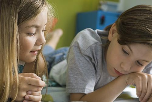 Två barn läser bok tillsammans.