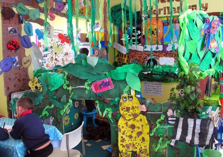 Barn sitter och ritar i ateljé som är full av pappersträd.