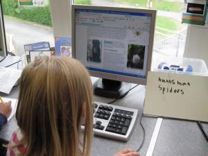 Flicka sitter framför dator.