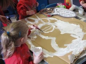 Elever målar med färg på kartong.