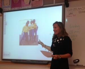 Kvinna står vid projicerad presentation framme i klassrum.
