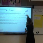 Kvinna skriver på smartboard längst fram i klassrummet.