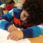 Elev skriver koncentrerat på papper.